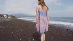 Het mooie meisje kijkt rond op een zwart strand van vulkanisch zand stock footage