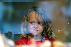Het mooie meisje kijkt in het venster van een winkel in OIA, en maakt grappige gezichten stock afbeelding