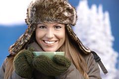 Het mooie meisje kleedde omhoog het warme het drinken thee glimlachen Stock Afbeeldingen