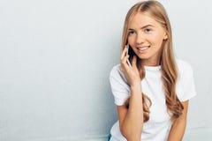 Het mooie meisje kleedde zich in een witte t-shirt, die op de telefoon, op een grijze achtergrond spreken royalty-vrije stock afbeelding