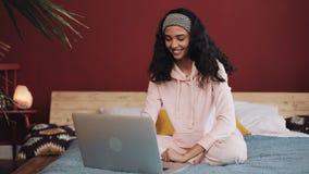 Het mooie meisje kleedde zich in roze pyjama's thuis gebruikend laptop computerzitting in bed De jonge vrouw glimlacht en babbelt stock footage