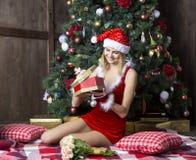 Het mooie meisje kleedde zich in santakostuum dichtbij Kerstmisboom Royalty-vrije Stock Afbeelding