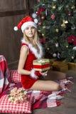 Het mooie meisje kleedde zich in santakostuum dichtbij Kerstmisboom Stock Foto's