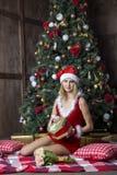 Het mooie meisje kleedde zich in santakostuum dichtbij Kerstmisboom Royalty-vrije Stock Foto