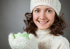Het mooie meisje koud voelen en het houden van een kop van hete drank Stock Foto