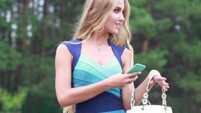 Het mooie meisje krijgt uit de zak mobiele telefoon stock videobeelden