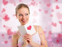 Het mooie meisje leest een prentbriefkaarvalentijnskaart Royalty-vrije Stock Afbeelding