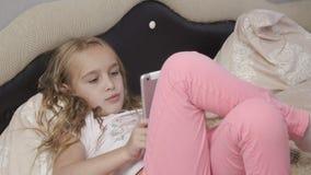 Het mooie meisje legt in bed met tablet stock videobeelden