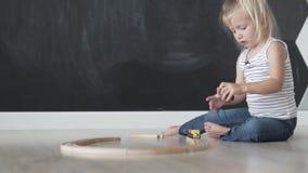 Het mooie meisje legt een houten weg voor de trein in de spelruimte aan stock videobeelden