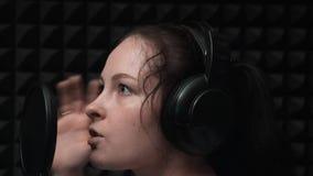 Het mooie meisje leidt op om lied in professionele studio te registreren Het meisje in muziekstudio zingt in hoofdtelefoons Pop c stock video