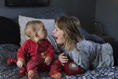 Het mooie meisje liggende op luid bed lachen uit en haar leuke mollige babyzuster die in pyjama op bed zitten stock fotografie