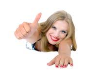 Het mooie meisje ligt en toont O.K. geïsoleerdc teken Stock Foto's