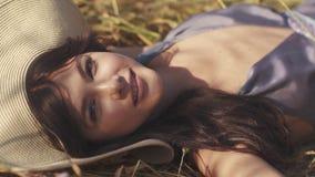 Het mooie meisje ligt met gesloten ogen in een wheaten gebied opent haar ogen en glimlacht bij de camera De gelukkige jonge zakke stock video