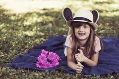 Het mooie meisje ligt op een deken in het park Stock Afbeeldingen