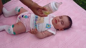 Het mooie meisje ligt op een roze deken in de tuin op het gras Het mamma geeft kind aan drinkt thee van een fles stock videobeelden