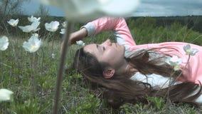 Het mooie meisje ligt op het groene gras in witte bloemen Een jonge vrouw rust op aard Schoonheid op een bloemweide stock videobeelden