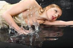 Het mooie meisje ligt op natte vloer Royalty-vrije Stock Foto's