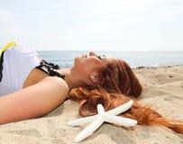 Het mooie meisje ligt op overzeese kust met shells aardvakantie Stock Fotografie