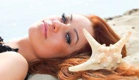 Het mooie meisje ligt op overzeese kust met shells aardvakantie Stock Foto's
