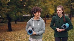 Het mooie meisje loopt in park met de holdingsmatten die van de yogainstructeur het gesturing en het lachen spreken Leraar-studen stock videobeelden