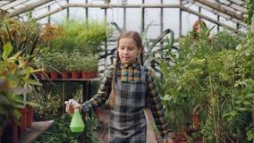 Het mooie meisje loopt in serre en bespuitend water op groen terwijl haar bezige moeder op achtergrond werkt stock videobeelden
