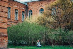 Het mooie meisje in lotusbloem stelt zit op de achtergrond van een oud gebouw en een jonge tot bloei komende boom stock afbeelding