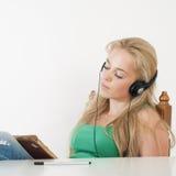 Het mooie meisje luisteren aan muziek en leert Stock Foto