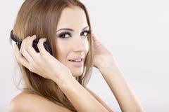 Het mooie meisje is luistert aan de muziek Stock Foto