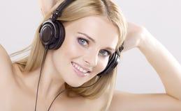 Het mooie meisje is luistert aan de muziek Stock Foto's