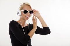 Het mooie meisje is luistert aan de muziek Royalty-vrije Stock Afbeeldingen