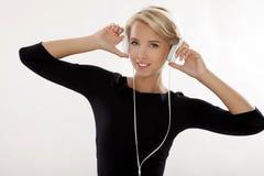 Het mooie meisje is luistert aan de muziek Royalty-vrije Stock Afbeelding