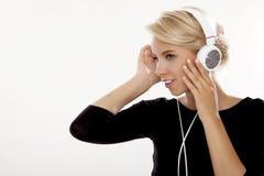 Het mooie meisje is luistert aan de muziek Stock Fotografie