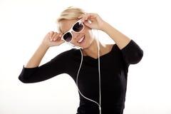 Het mooie meisje is luistert aan de muziek Stock Afbeelding