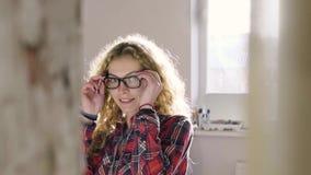 Het mooie meisje maakt het bed in de ochtend schoon en draagt glazen stock footage