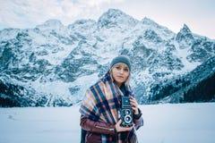 Het mooie meisje maakt een foto op een oude uitstekende camera In de bergen in de winter, avontuur en reis stock afbeeldingen