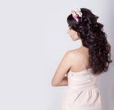 Het mooie meisje maakt haar haarkrullen op lang zwart die haar met een kroon van bloemen wordt verfraaid Royalty-vrije Stock Afbeeldingen