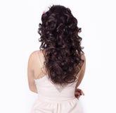 Het mooie meisje maakt haar haarkrullen op lang zwart die haar met een kroon van bloemen wordt verfraaid Royalty-vrije Stock Foto