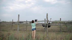 Het mooie meisje maakt video op de tabletstruisvogel bij het landbouwbedrijf stock videobeelden