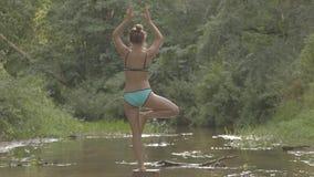 Het mooie meisje mediteert op water in het midden van de bosrivier stock videobeelden