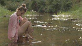 Het mooie meisje mediteert op water in het midden van de bosrivier stock footage