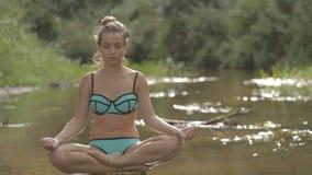Het mooie meisje mediteert op water in het midden van de bosrivier stock video