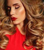 Het mooie meisje met blond krullend haar en heldere avondmake-up, draagt elegante kleding royalty-vrije stock foto's