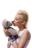 Het mooie meisje met blonde hairand en het stuk speelgoed dragen Stock Fotografie