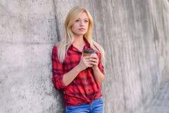 Het mooie meisje met blondehaar, grote hazelaarogen, met een kop in haar handen heeft een onderbreking van het werk Zij droomt ov royalty-vrije stock afbeelding