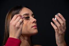 Het mooie meisje met bruin haar, terwijl het zetten van mascara op haar ogen royalty-vrije stock foto