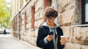 Het mooie meisje met donker krullend haar gebruikt smartphone texting vrienden en houdt koffie lopend in alleen stad modern stock footage
