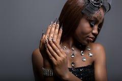 Het mooie meisje met donkere huid en de lange acrylspijkers in een zwarte kleden zich in de studio Royalty-vrije Stock Fotografie