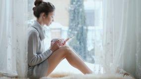 Het mooie meisje met een kop van koffie en de tablet ontspannen dichtbij het venster stock footage
