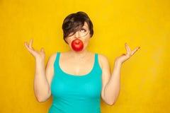 Het mooie meisje met een kort kapsel met rood Apple in haar mond verzoekt een gezonde levensstijl een vrouw houdt sappig groot Ap stock fotografie