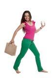 Het mooie meisje met een zak en een koffiekop is gang Stock Foto